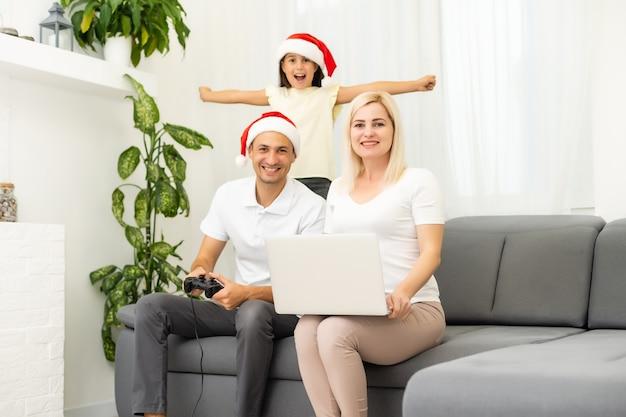 Glückliche familie, die zu hause videospiele spielt und zusammen spaß hat. weihnachten