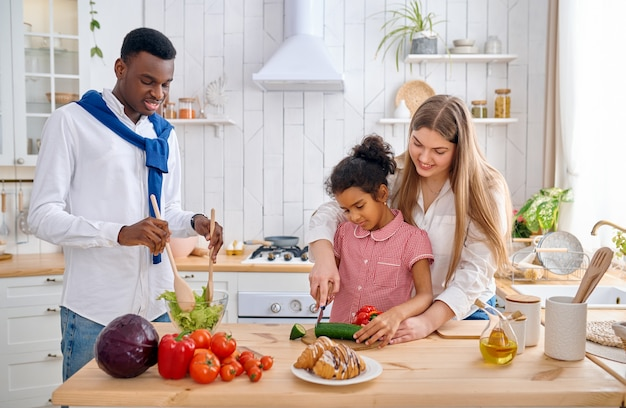 Glückliche familie, die zum frühstück gemüsesalat kocht. mutter, vater und ihre tochter morgens in der küche, gute beziehung