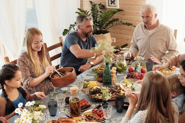 Glückliche familie, die zusammen am festlichen tisch sitzt und verschiedene gerichte zu hause isst