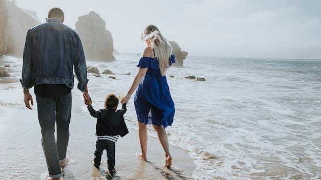Glückliche familie, die zusammen am strand spazieren geht