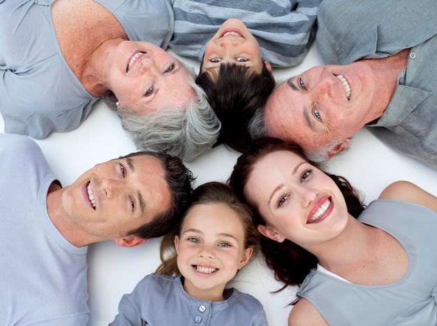 Glückliche familie, die zusammen auf boden mit köpfen liegt