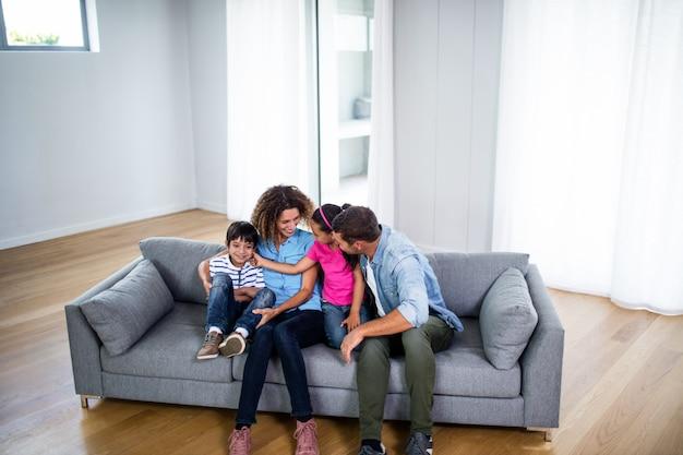 Glückliche familie, die zusammen auf sofa sitzt