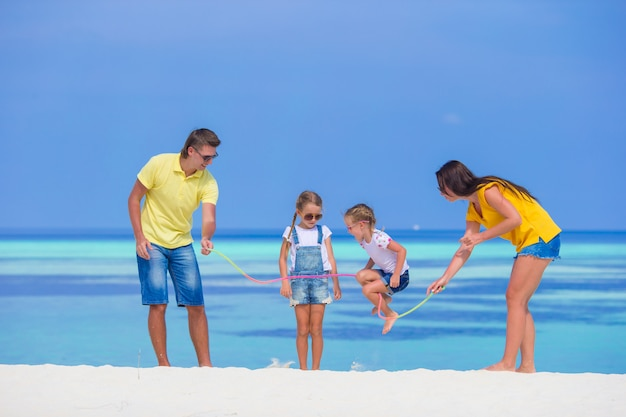 Glückliche familie, die zusammen auf weißem strand spielt