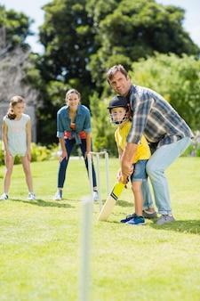 Glückliche familie, die zusammen cricket spielt