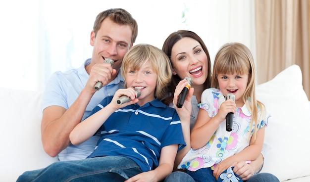Glückliche familie, die zusammen ein karaoke singt