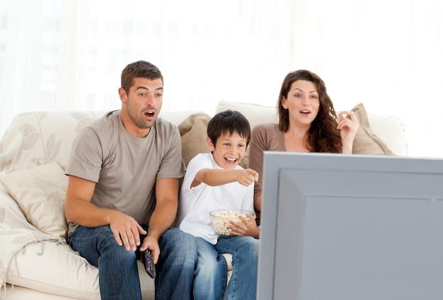 Glückliche familie, die zusammen einen film im fernsehen auf dem sofa aufpasst