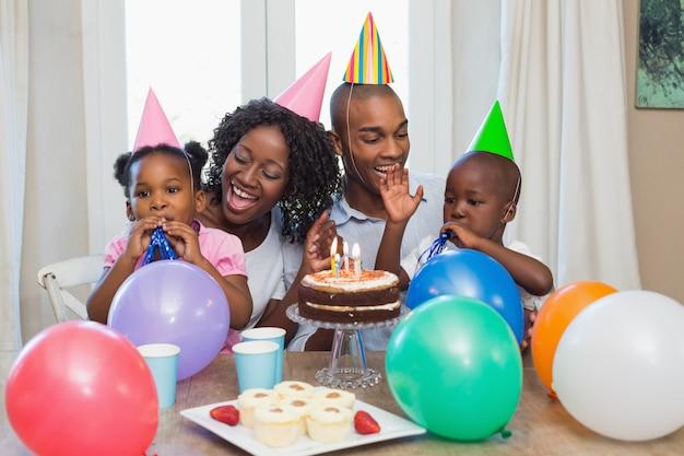 Glückliche familie, die zusammen einen geburtstag am tisch feiert