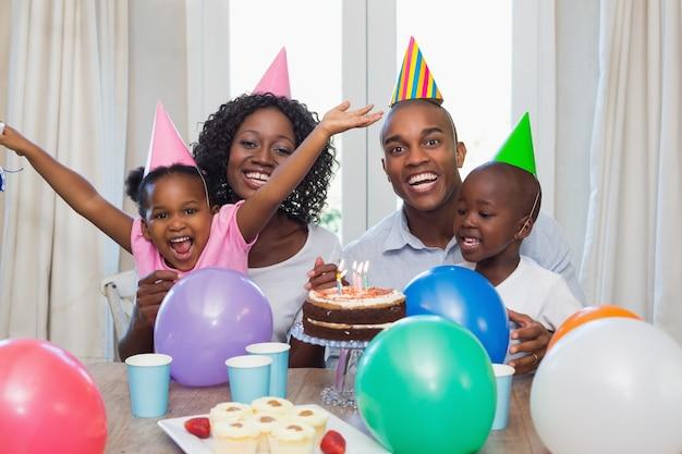 Glückliche familie, die zusammen einen geburtstag bei tisch feiert