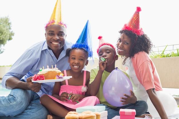 Glückliche familie, die zusammen einen geburtstag im garten feiert