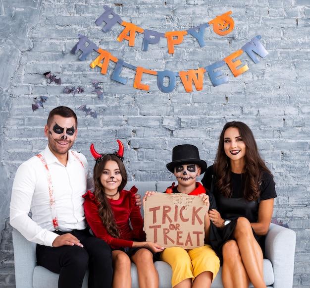 Glückliche familie, die zusammen für halloween aufwirft