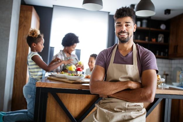 Glückliche familie, die zusammen gesundes essen in der küche kocht