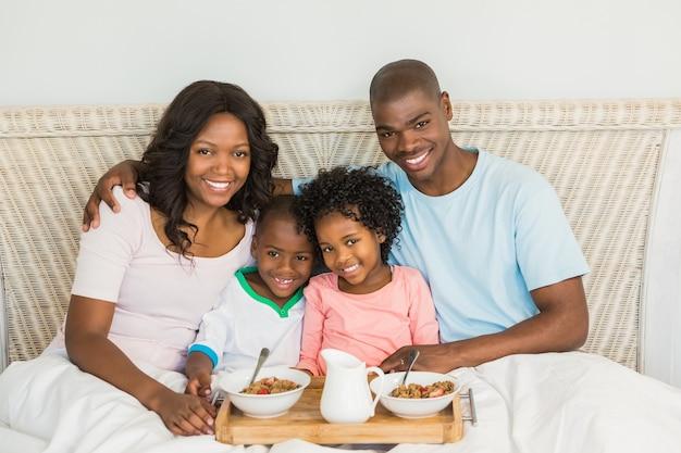 Glückliche familie, die zusammen im bett frühstückt