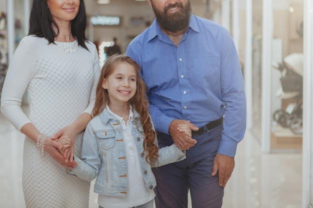 Glückliche familie, die zusammen im einkaufszentrum kauft
