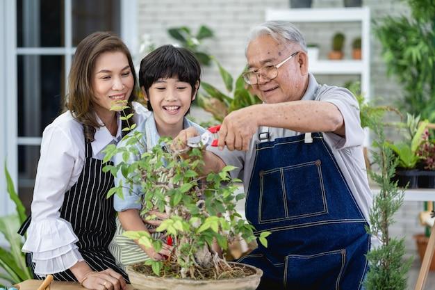 Glückliche familie, die zusammen im garten gärtnert, großvater-enkel und frau, die sich um die natur kümmern