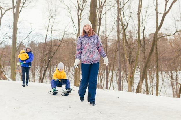 Glückliche familie, die zusammen im winterpark geht, zwei erwachsene mann und frau und zwei kinder