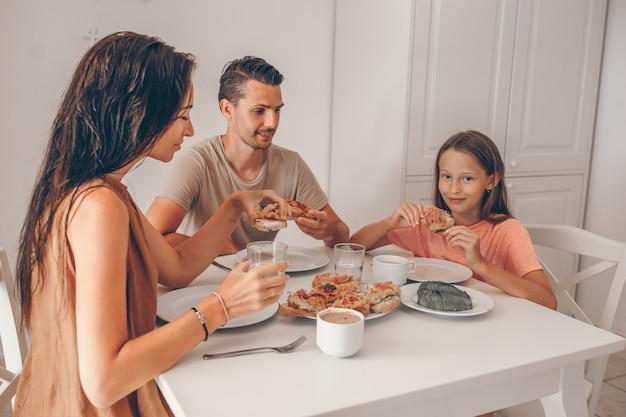 Glückliche familie, die zusammen in der küche frühstückt