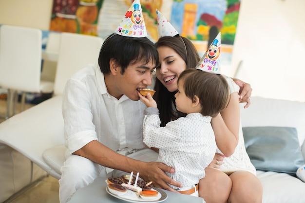 Glückliche familie, die zusammen kuchen zum geburtstag des sohnes isst