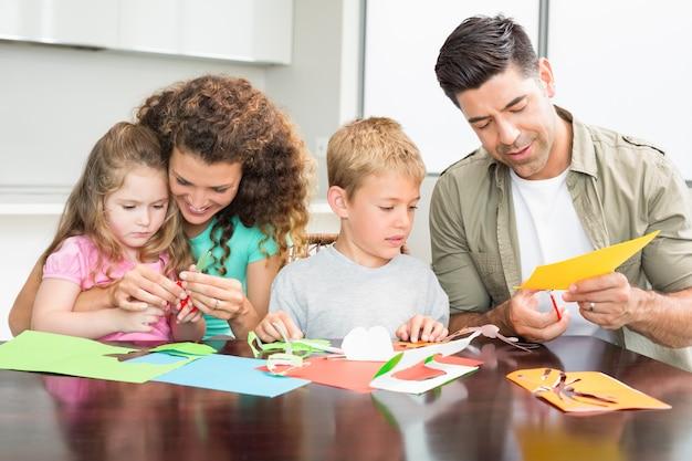 Glückliche familie, die zusammen künste und handwerk am tisch zu hause in der küche tut