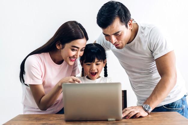 Glückliche familie, die zusammen laptop laptop betrachtet und betrachtet