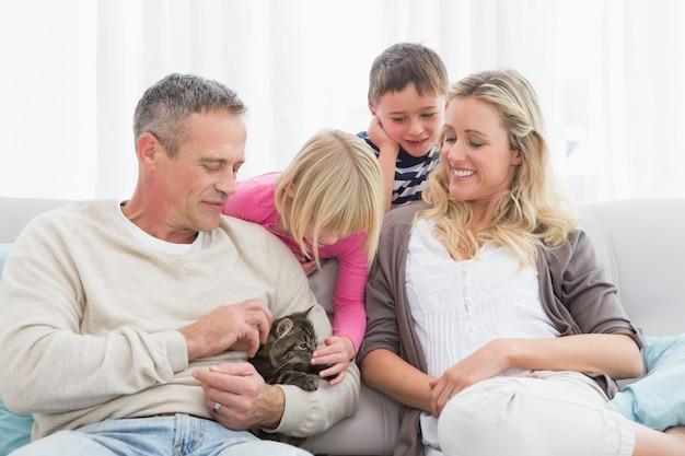 Glückliche familie, die zusammen mit haustierkätzchen sitzt