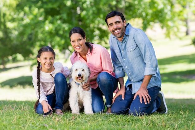 Glückliche familie, die zusammen mit ihrem haustierhund im park genießt