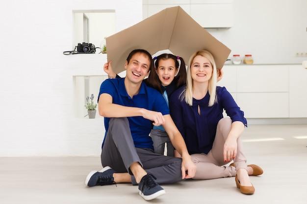 Glückliche familie, die zusammen sitzt und das hauszeichen macht
