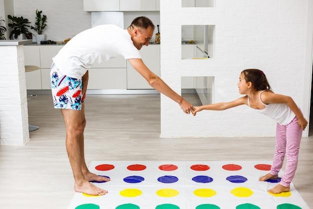 Glückliche familie, die zusammen spaß hat und zu hause twister-spiel spielt