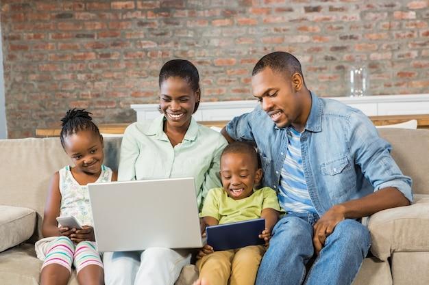 Glückliche familie, die zusammen technologie einsetzt