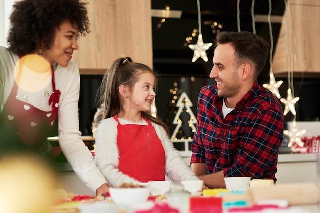 Glückliche familie, die zusammen weihnachtsplätzchen macht
