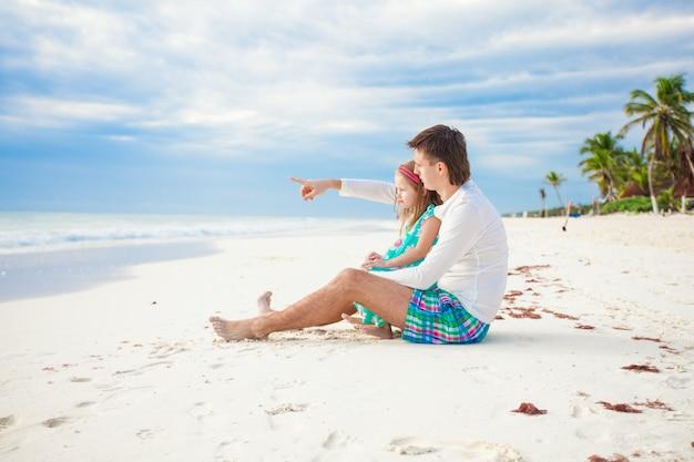 Glückliche familie, die zusammen zeit am weißen strand genießt