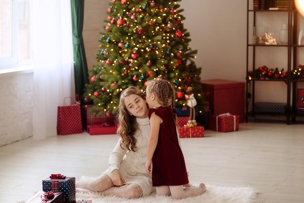 Glückliche familie durch den weihnachtsbaum zu hause mit geschenken