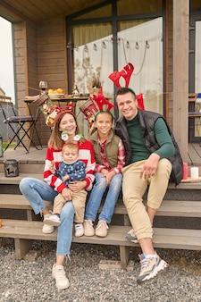 Glückliche familie. eine süße familie, die auf der haustreppe sitzt und glücklich aussieht