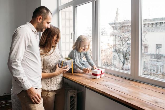 Glückliche familie, eltern spielen mit geschenkbox mit ihrer tochter zu hause nahe fenster