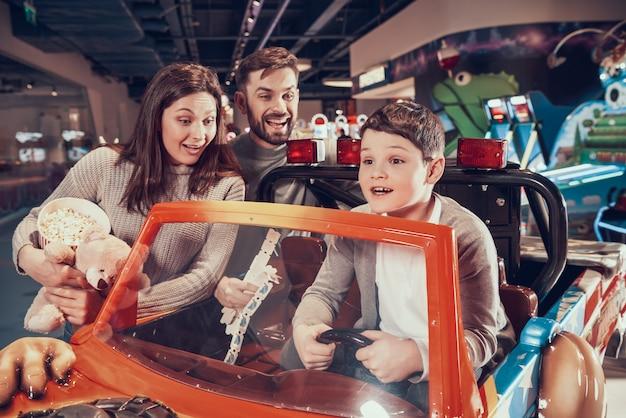 Glückliche familie, entzückter sohn, der auf spielzeugauto sitzt