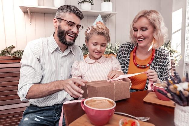 Glückliche familie. erfreute positive eltern, die um ihre tochter sitzen und ihr ein geschenk geben