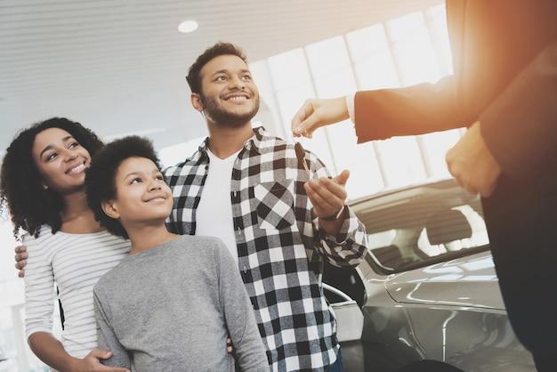 Glückliche familie erhält schlüssel. afro-leute kaufen auto.