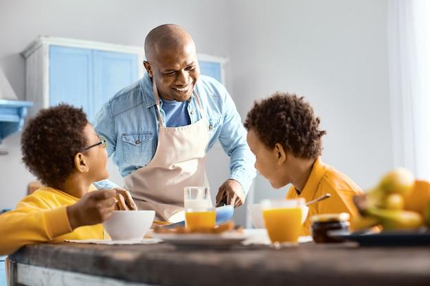 Glückliche familie. fröhlicher junger mann, der mit seinen kindern spricht und ihnen omelett anbietet, während sie frühstücken