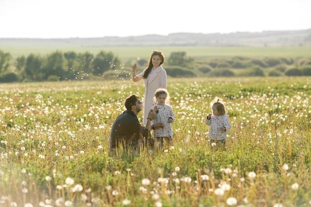 Glückliche familie geht auf dem feld spazieren und spielt mit löwenzahn.