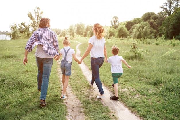Glückliche familie geht die straße in der wiese hinunter. eltern halten ihre kinder an den händen. sie springen und genießen den moment.