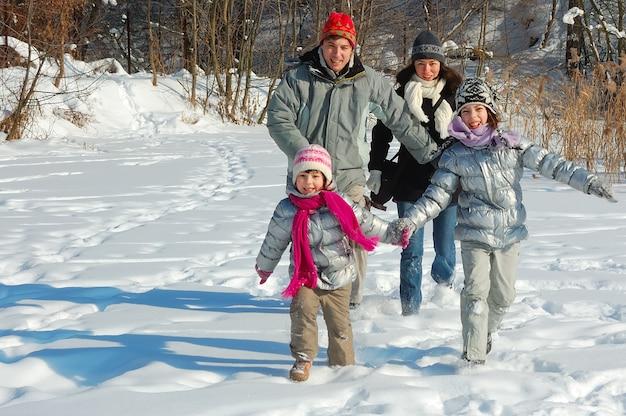 Glückliche familie geht im winter, hat spaß und spielt mit schnee draußen am feiertagswochenende