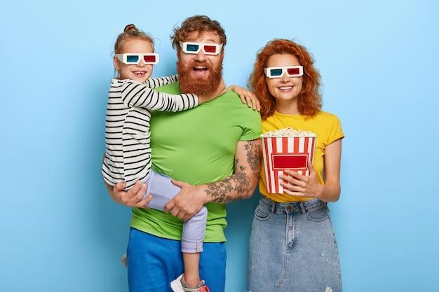 Glückliche familie genießen film oder zeichentrickfilm im kino, tragen 3d-brille, amüsiert durch kühlen ton und visuelle effekte, essen köstlichen snack. kleines mädchen auf vaters händen, umarmt ihn. menschen, freizeit, wochenende