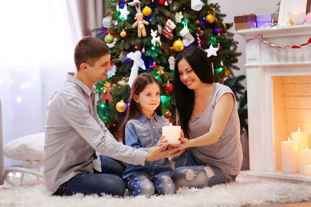 Glückliche familie hält zusammen eine kerze in den händen im dekorierten weihnachtsraum