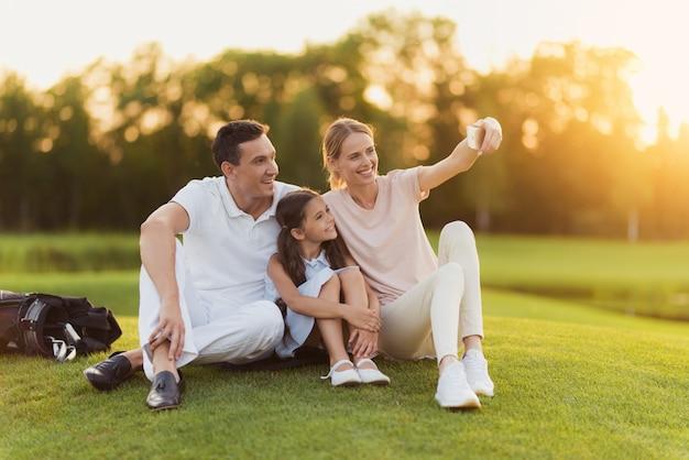 Glückliche familie hat ruhe nach dem golfen nimmt selfie.