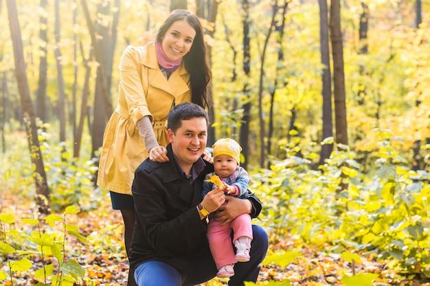 Glückliche familie im freien im herbst. baby und mutter und vater