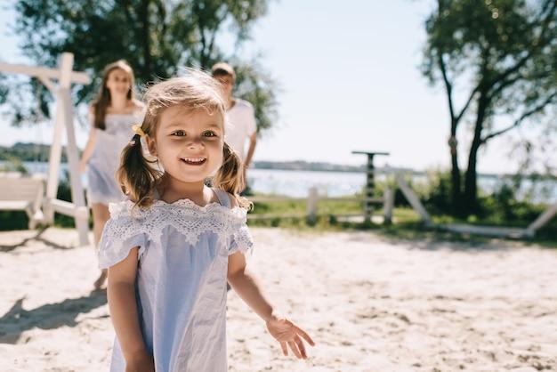 Glückliche familie im freien verbringen zeit zusammen. vater, mutter und tochter haben spaß und spielen am strand