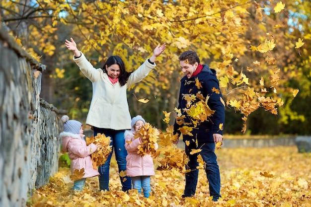 Glückliche familie im herbstpark. mutter, vater und zwei kleine mädchen auf der natur werfen gelbe blätter, spielen, lachen.