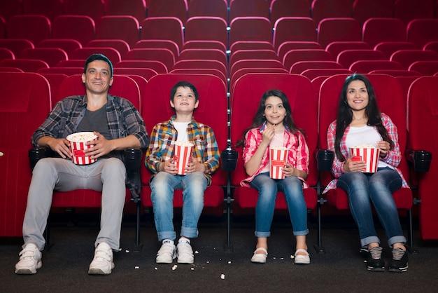 Glückliche familie im kino sitzen