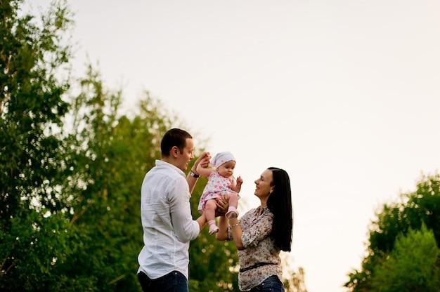 Glückliche familie im parkabendlicht