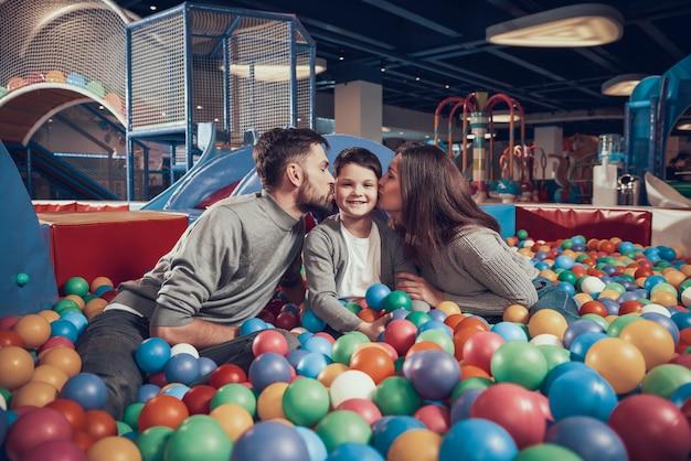 Glückliche familie im pool mit bällen stehen zusammen still.