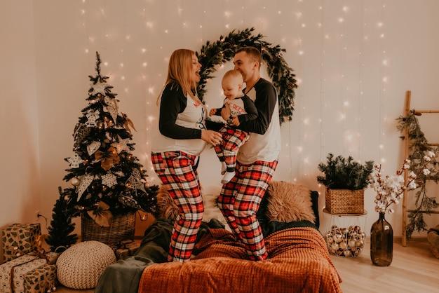 Glückliche familie im pyjama mit kindereltern spielen mit kind, das auf bett im schlafzimmer springt. neujahr familienkleidung sieht outfits. valentinstag feier geschenke